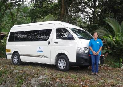 Lilliana in front of white 9 passenger van