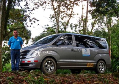 Driver in blue shirt standing next to van next to the rainforest