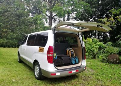 White van with rear door open in tropical garden